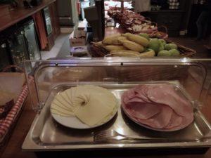wurst und käse beim frühstücksbuffet im swiss cottage hostel